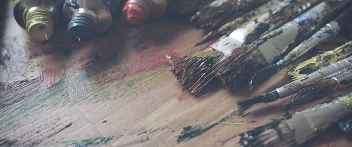 Paintbrushes and paints on a wooden table